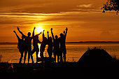 Group of happy friends hands up against the sunset.