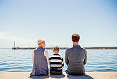 Rear view of young family with son sitting on concrete pier outdoors by the sea.