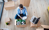 Top view of mature man with boxes moving in new house, unpacking.
