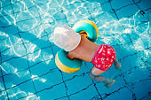 Top view of small child with armbands in swimming pool on summer holiday.