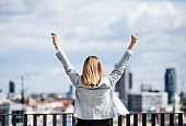 A rear view of young businesswoman standing on a terrace, expressing excitement.