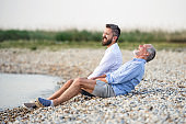 Senior father and mature son sitting by the lake. Copy space.