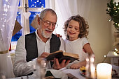 Senior grandfather with small granddaughter indoors at Christmas, reading Bible.