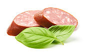 Smoked sausage slices with basil herb, isolated on white background.