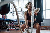 At the morning time. Blonde sport woman have exercise with ropes in the gym. Strong female