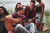 Guitarist in center of everyone's attention. Group of people have picnic on the beach. Friends have fun at weekend time