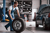 Man with beard rolls tire. Employee in the blue colored uniform works in the automobile salon