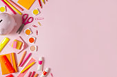 School Supplies and Piggy Bank on Soft Pink Background