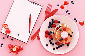 Pancake with blueberry and strawberry in the plate with clipboard on pink pastel background. 3d render