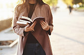 Young attractive faceless brunette girl holding a small stack of books and reading a brown one, while standing in autumn park with trees at the blurry background with a copy space
