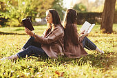 Side view of young pretty brunette twin sisters sitting back to back on the grass with legs slightly bent in knees reading brown books and wearing casual coat in autumn sunny park on blurry background