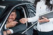 Can't handle emotions. Happy owner of new car sitting inside and takes keys from female manager