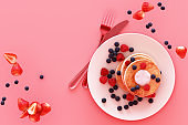Pancake with blueberry and strawberry in the plate on pink pastel background. 3d render