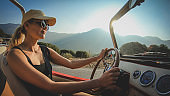 Smiling woman in sunglasses with blond hair drives a car without a roof