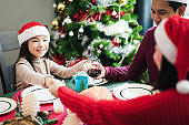 Young Asian family celebration in Christmas day, father mother and daughter pray and touch hand before have a meal breakfast in kitchen at home in morning time. felling love and happy. Merry Xmas.