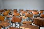 Tables and chairs in the university classroom are empty