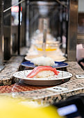 sushi that Japanese rice topping with sea fish placed in a white plate that placed on the belt