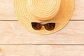 Sunglasses and a straw hat on a wooden table. The concept of summer.