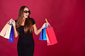 Shopping. Woman holding colored bags on red background in black friday holiday