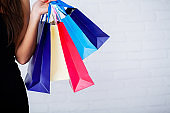 Shopping. Closeup of woman holding color paper shopping bag on white wall background