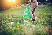 Woman Picking Up Trash in Rural Scene
