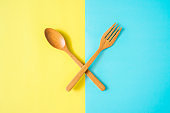 wooden spoon and fork on yellow and blue paper background, top view