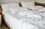 messy white blanket  on bed in bedroom in morning