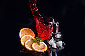 Hibiscus cold tea pouring into glass with ice, lemon and mint isolated on black background.
