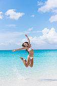 Fun bikini woman jumping on beach splashing water