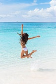 Happy beach vacation success woman jumping of joy