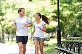 Friends couple happy running together in city park