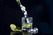 Summer cocktail mojito with splash on black background.