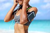 Fitness phone armband woman putting earphones