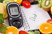Glucometer with result of sugar level, fruits with vegetables and notepad with word diet. Healthy food for diabetic concept