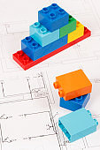 Colorful toy blocks and construction housing plan. Building, buying or renting home concept