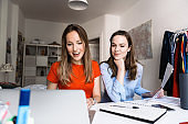 two young woman sitting  together in front of laptop
