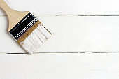 A brush with white paint on a wooden painted background, copy space, top view