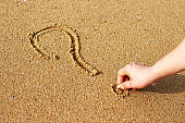 Male hand draws on sand question mark, top view
