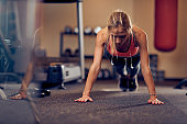 Sporty woman doing push-ups on the floor.