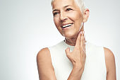 Senior woman posing in front of gray background.
