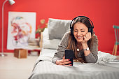 Woman listening music over smart phone in bedroom.