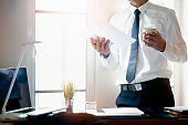 businessman holding paperwork and cup standing near office window with sunlight while working in modern office.