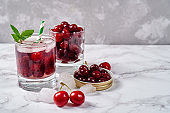 Fresh cherry lemonade with ice, mint and paper straw in sparkling glasses on gray table background, copy space. Cold summer drink. Berry cocktail