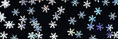 Banner for the site a black background with confetti in the form of snowflakes.