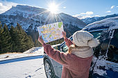Young woman looks at road map from insider car on snowy mountain road- road trip