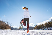 Rear view of woman trail running in winter