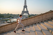 Sporty young man running up the stairs at the Eiffel Tower in Paris