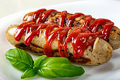 Two pork sausages with a lot of ketchup on plate