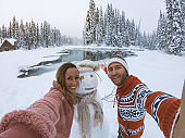 Couple taking selfie with snowman on winter vacations