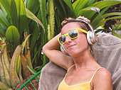 Girl listening to music in tropical garden- Young woman wearing wireless headphones and relaxing on lounge chair